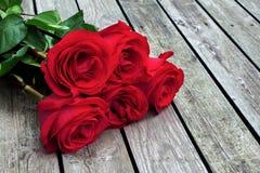 El manojo del rojo o del escarlata de rosas con verde se va en fondo de Imagenes de archivo