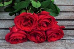 El manojo del rojo o del escarlata de rosas con verde se va en fondo de Imágenes de archivo libres de regalías