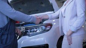 El mantenimiento profesional del coche, cliente femenino da llaves autos al técnico para la reparación y sacude las manos en la g almacen de video