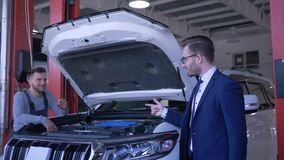El mantenimiento profesional del coche, técnico está reparando el vehículo con la capilla abierta y el dueño muestra gesto positi almacen de video