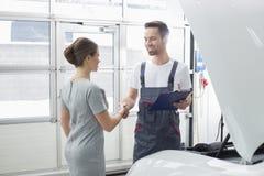 El mantenimiento sonriente dirige la sacudida de las manos con el cliente femenino en el taller de reparaciones del coche Imagenes de archivo