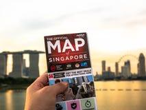 El mapa de la tenencia del hombre de Singapur y del fondo es horizonte de Singapur en la tarde en la ciudad de Singapur foto de archivo