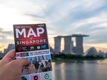 El mapa de la tenencia del hombre de Singapur y del fondo es horizonte de Singapur en la tarde en la ciudad de Singapur imagen de archivo