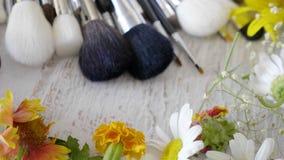 El maquillaje cepilla la colocación en la tabla de madera al lado de las flores metrajes