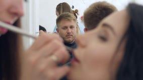 El maquillaje profesional, hombre joven mira el proceso de las pinturas del labio de la mujer en salón de belleza almacen de metraje de vídeo