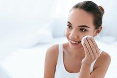 El maquillaje quita Piel de limpieza de la cara de la muchacha con el cojín cosmético imagen de archivo libre de regalías