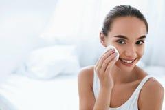 El maquillaje quita Piel de limpieza de la cara de la muchacha con el cojín cosmético fotografía de archivo