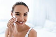 El maquillaje quita Piel de limpieza de la cara de la muchacha con el cojín cosmético foto de archivo