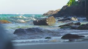 El mar agita el agua que salpica en la playa rocosa en la isla tropical Las ondas de agua que salpican en el océano costean el ma metrajes