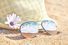 El mar agita en gafas de sol duplicadas elegantes en la arena Vacaciones de verano tropicales Día de verano en la playa imagen de archivo libre de regalías