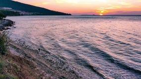 El mar agita en la playa arenosa en la puesta del sol 4K