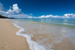 El mar agita la línea impacto del latigazo en la playa de la arena debajo del cielo azul Foto de archivo libre de regalías