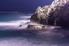 El mar agita la línea roca del latigazo del impacto en la playa en noche fotografía de archivo libre de regalías