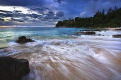 El mar agita la línea roca del latigazo del impacto en la playa Imagenes de archivo