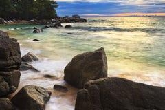 El mar agita la línea roca del latigazo del impacto en la playa Foto de archivo