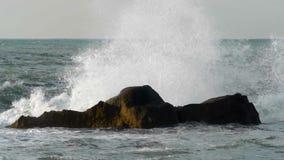 El mar agitado que machaca las rocas con alto salpica