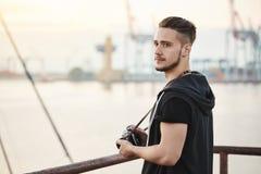 El mar atrae a este fotógrafo Retrato al aire libre del individuo joven atractivo que se coloca en puerto, gozando mirando el mar imagen de archivo libre de regalías