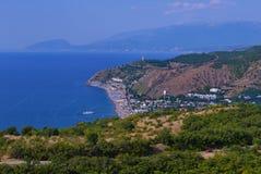 El mar azul sin fin, lavando las orillas de una ciudad de vacaciones grande contra el contexto de altas montañas imagen de archivo