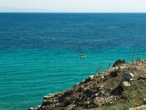 El mar azul sin fin y la orilla rocosa Imagenes de archivo