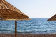 El mar con los paraguas de la paja del mar del sunThe con los paraguas de la paja del sol foto de archivo libre de regalías
