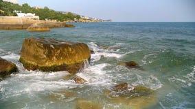El mar de la cámara lenta agita salpicar contra rocas en el cielo azul almacen de metraje de vídeo