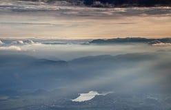 El mar de nubes, de la niebla y del sol irradia en la puesta del sol, lago sangrado, Eslovenia foto de archivo