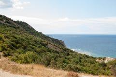 El mar en un área montañosa con los árboles por la tarde imagenes de archivo