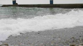 El mar espumoso agita extendiendo por la playa en wather nublado metrajes