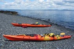 El mar kayaks en una playa rocosa en puerto de la barra Imagen de archivo