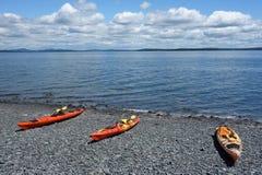 El mar kayaks en una playa rocosa en puerto de la barra Fotos de archivo libres de regalías