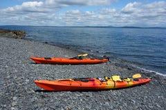 El mar kayaks en una playa rocosa en puerto de la barra Foto de archivo