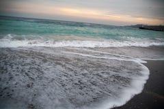 El mar tempestuoso de la turquesa con hacer espuma agita en la puesta del sol Fotos de archivo