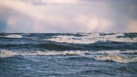 El mar tempestuoso en invierno con blanco agita el machacamiento - lo de la película del vintage fotos de archivo