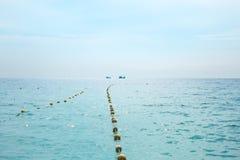 El mar y el cielo, junto con los barcos de pesca que miran lejos Foto de archivo libre de regalías