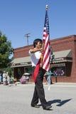 El marchar con la bandera de los E.E.U.U. Imagenes de archivo