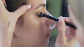 El marco cosechado primer, la cara de una chica joven, ella hace maquillaje en un salón de belleza El artista de maquillaje con u almacen de metraje de vídeo