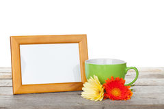 El marco de la foto con la taza de café y de gerbera florece Fotografía de archivo