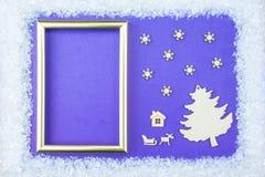 El marco de la Navidad consiste en los adornos blancos: copos de nieve, reno, y cajas de regalo en fondo azul E Foto de archivo libre de regalías