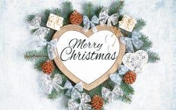 El marco de la Navidad en la forma de un coraz?n es rodeado por las ramas de las decoraciones del A?o Nuevo de una Navidad del ?r imagenes de archivo