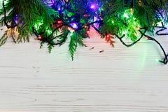 El marco de la Navidad de la guirnalda se enciende en ramas del abeto borde elegante Fotografía de archivo