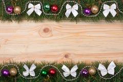 El marco de la Navidad hecho de las ramas del abeto adornadas con blanco arquea gotas y bolas en un fondo de madera ligero Foto de archivo libre de regalías