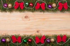 El marco de la Navidad hecho de las ramas del abeto adornadas con rojo arquea gotas y bolas en un fondo de madera ligero Foto de archivo libre de regalías