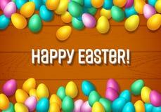 El marco de Pascua con los huevos felices coloridos brillantes extendió por de madera