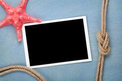 El marco en blanco de la foto con las estrellas de mar y la nave rope Imagen de archivo