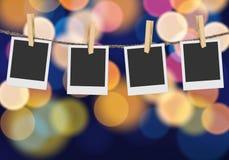 El marco en blanco de la foto en multicolor defocused borroso enciende el fondo Imagenes de archivo