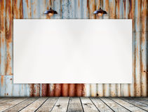 El marco en blanco en Rusted galvanizó la placa del hierro con el piso de madera Fotografía de archivo libre de regalías