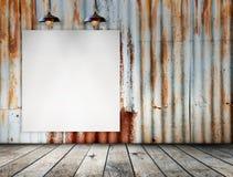 El marco en blanco en Rusted galvanizó la placa del hierro con el piso de madera Imagen de archivo libre de regalías