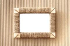 El marco hecho a mano de la foto trenzó el yute contra fondo del panel de fibras de madera acanalado Imagen de archivo