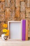 El marco, los libros y las flores de la foto en la tabla de madera con rojo envejecieron Imágenes de archivo libres de regalías