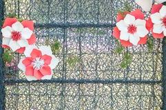 El marco metálico del primer con la flor artificial para adorna en el fondo texturizado jardín Imagenes de archivo